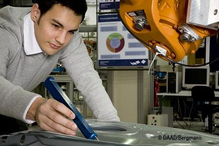Student Andreas Putzer bedient in der TUM einen Roboterarm und vermisst hierfür eine Autotür