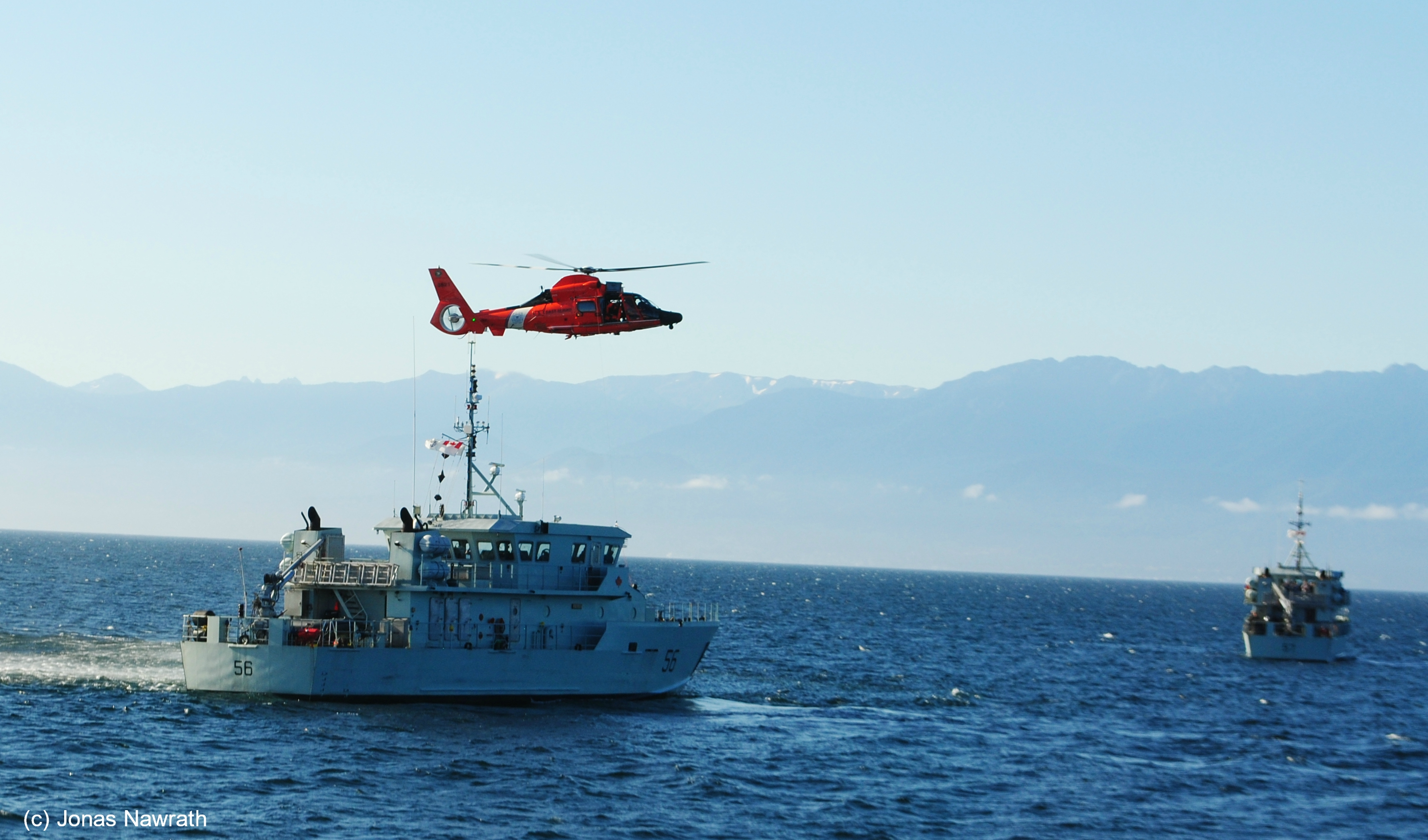 A red military helicopter flies over a military vessel