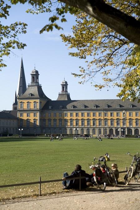 Hauptgebäude mit Hofgarten und Studenten mit Fahrrädern.  *** Local Caption ***